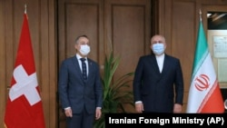 IRAN -- Iranian Foreign Minister Mohammad Javad Zarif, right, and his Swiss counterpart Ignazio Cassis wearing protective face masks to help prevent spread of the coronavirus pose for media prior to their meeting in Tehran, September 7, 2020