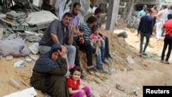 Палестинцы на фоне разрушенных зданий в секторе Газа.