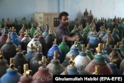 An Afghan man refills oxygen cylinders at a factory as demand skyrockets in Jalalabad on June 28.