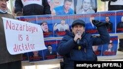 """Оралда әкімдік рұқсатымен өткен митингіде """"Nazarbayev is a dictator"""" деген плакат ұстап тұрған адам. 28 ақпан, 2021 жыл."""