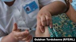 Дарыгер коронавируска каршы вакцинаны сайып жатат. Кыргызстан.