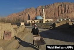A Hazara man pushes a wheelbarrow along a road in Bamiyan Province.