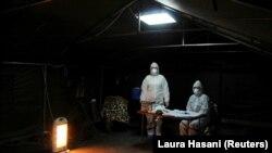 Dy punëtorë shëndetësorë në një tendë për ofrim të ndihmës për personat që dyshohet se janë infektuar me koronavirus.