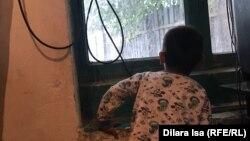 Младший сын Меирбека Отеганова смотрит на улицу через окно. Туркестанская область, 30 сентября 2020 года.