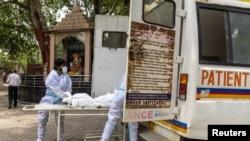 کارکنان صحی هند در حال انتقال جسد فردی که در اثر ابتلا به ویروس کرونا جان باخته است