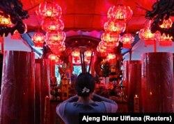 Віряни використовують святкові аромапалички у храмі в Джакарті, Індонезія, 11 лютого 2021 року