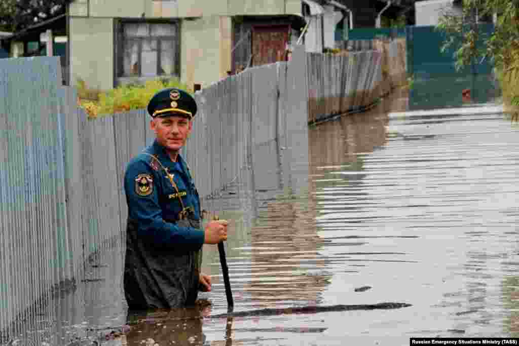 A employee from the Russian Emergency Situations Ministry inspects a flooded street in the Nanaisky district of the Khabarovsk region on September 16. (TASS)