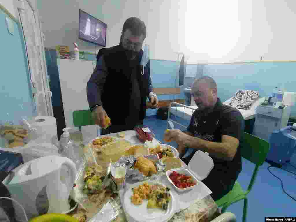 """Doru și Daniel, pacienți covid internați la Spitalul """"Caritas"""" din Roșiori de Vede/Teleorman, iau cina. Pachetele cu mâncare ajung la pacienți cu ajutorul infirmierelor, care o dată pe zi lasă pachetele la ușa fiecărei secții carantinate."""