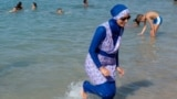 RELIGION-BURQA/FRANCE/A woman wearing a burkini walks in the water August 27, 2016 on a beach in Marseille, France, the day after the country's highest administrative court suspended a ban on full-body burkini swimsuits that has outraged Muslims and opene