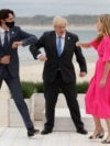 Britain's Prime Minister Boris Johnson, his spouse Carrie Johnson and Canada's Prime Minister Justin Trudeau bump elbows during the G7 summit in Carbis Bay, Cornwall