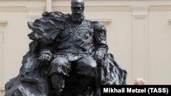 Памятник с орденом в виде шестиконечной звезды и Путин