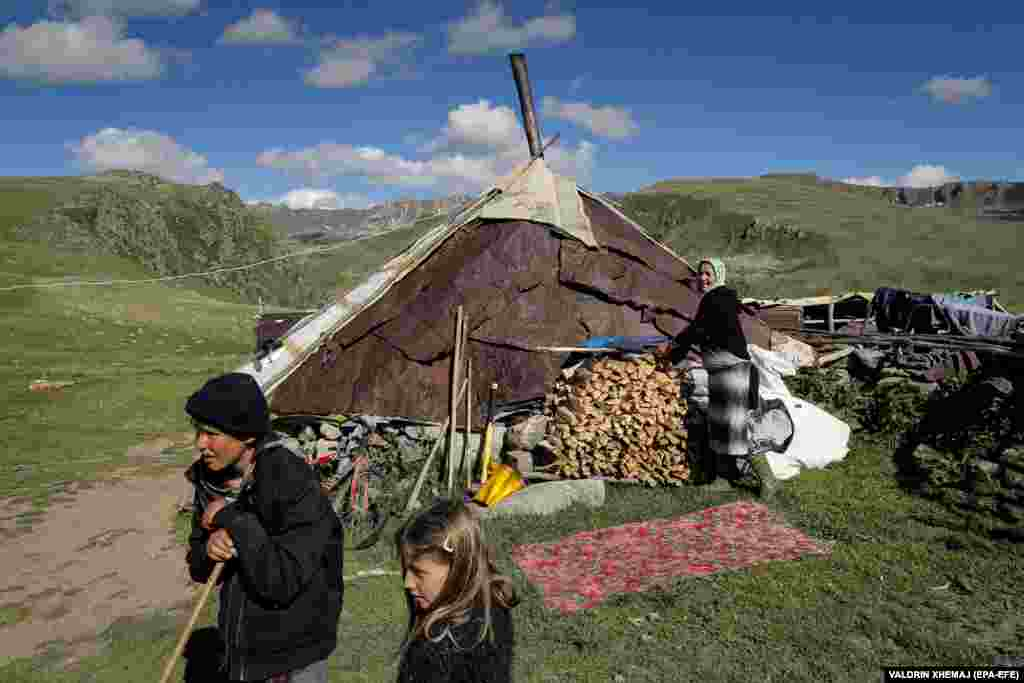 Borjan Bajle (left) watches the flock graze on a pasture near the hut.