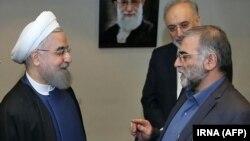 محسن فخریزاده (سمت راست) در مراسم دریافت نشان خدمت از حسن روحانی