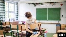 Fertőtlenítenek egy tanteremben a fővárosi Krúdy Gyula Angol - Magyar Két Tanítási Nyelvű Általános Iskolában 2020. október 28-án.