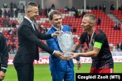Szijjártó Péter külügyminiszter a másodosztályú bajnoki serleget nyújtja át Dzsudzsák Balázs debreceni focistának 2021. május 6-án. Középen Bánki Erik fideszes képviselő.