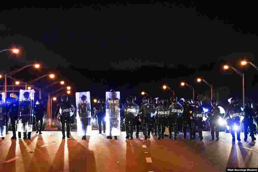 Поліцейські, прикриваючись щитами, просуваються, щоб розблокувати блокування руху на автостраді під час мітингу проти расової нерівності.Атланта, штат Джорджія, США
