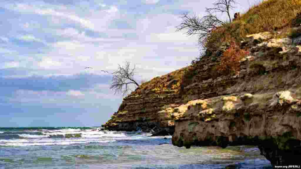 Каменистый берег обрамляет пляжную зону села с юго-востока