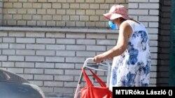 Idős asszony kerül meg egy szabálytalanul parkoló autót a XX. kerületi Tátra téren 2020. szeptember 5-én.