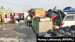"""""""Ақ бұлақ"""" базарының сыртында ыстық самса мен сусын сатып тұрған әйел. Алматы, 24 желтоқсан 2020 жыл."""