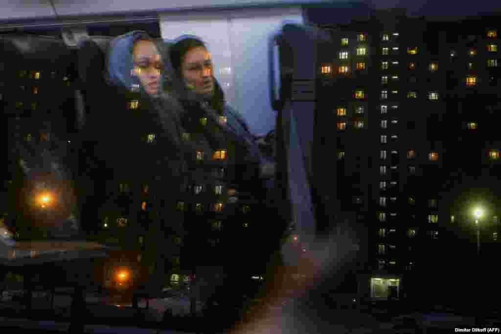 Две женщины едут поездом по окраине Москвы