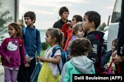 Russian children from the Al-Hawl camp are handed over to a delegation from their country in the northeastern Syrian city of Qamishli last month.
