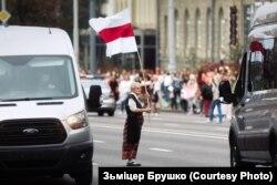 Палітычная актывістка 74-гадовая Ніна Багінская з бел-чырвона-белым сьцягам падчас «жаночага маршу». Менск, жнівень 2020 году