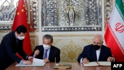 Iranian Foreign Minister Mohammad Javad Zarif (right) and his Chinese counterpart, Wang Yi, sign a cooperation agreement in Tehran on March 27.