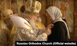 Светлана Полякова ҳангоми гирифтани ҷоиза аз патриарх Кирилл, соли 2014