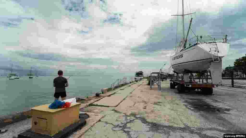Самотній молодий рибалка на все тому ж причалі
