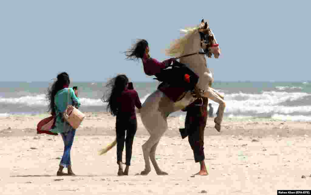 A girl rides a horse on a beach in Karachi, Pakistan. (epa-EFE/Rehan Khan)