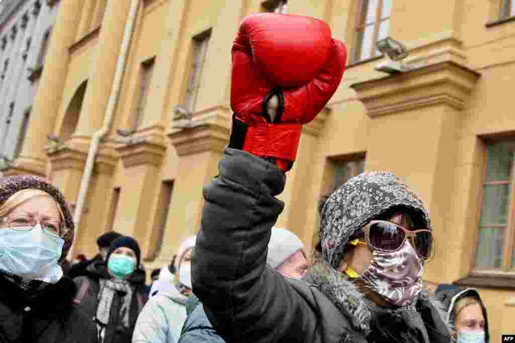 A woman wearing a boxing glove takes part in a rally against police violence by Belarusian pensioners in Minsk on November 23. (AFP)