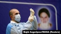 Një zyrtar iranian i shëndetësisë duke mbushur një shiringë me vaksinën ruse kundër koronavirusit, Sputnik V, në Teheran. Shkurt, 2021.