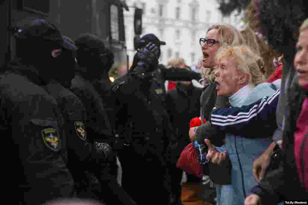 Activists argue with law enforcement officers during a rally in support of detained Belarusian opposition leader Maryya Kalesnikava in Minsk on September 8. (Tut.by via Reuters)