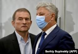 Viktor Medvedcsuk ukrán képviselő (bal oldalt) beszélget az Ellenzéki Platform az Életért parlamenti frakciójának vezetőjével, Jurij Bojkóval a kijevi fellebbviteli bíróságon egy tárgyaláson Kijevben, 2021. május 21-én. A bíróság azt a fellebbezést tárgyalta, amelyet a hazaárulással gyanúsított 66 éves üzletember, Medvedcsuk házi őrizetbe helyezéséről szóló határozat ellen nyújtottak be. A törvényhozó, aki Vlagyimir Putyin orosz elnököt személyes barátai közé sorolja, azt mondta, hogy az ellene felhozott vádak politikai indíttatásúak, és az álláspontja miatt büntetik