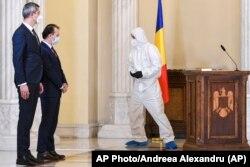 Az új román miniszterelnök és helyettese beiktatásukon figyelik, ahogy a teremben zajlik a fertőtlenítés