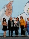 IRAQ - Iraqi Christians pose for photo near a mural of Pope Francis on the wall of a church upon his upcoming visit to Iraq, in Baghdad, Iraq February 22, 2021