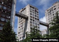 Многоэтажные дома в холмистом пригороде Тбилиси с «небесным мостом». Архитектурное решение обеспечивает быстрое и простое перемещение между верхним холмом и соседними районами, без утомительного подъема или спуска по склону. Люди могут подняться на лифте, а затем пройти по мосту через расположенный в высотке продуктовый магазин на вершину ближайшего холма.