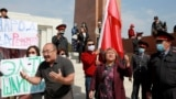 A group of protesters shout slogans urging people to vote against all parties during a rally in Bishkek ahead of upcoming parliamentary elections, which are scheduled for October 4.