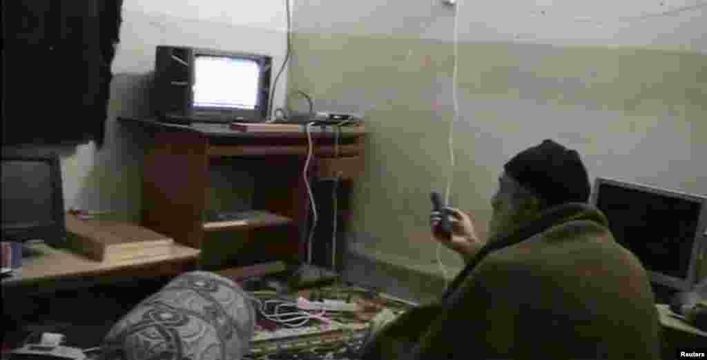 Бин Ладен смотрит на самого себя по телевизору, вероятно, в своем убежище в Абботтабаде, Пакистан, на домашнем видео без даты. Исламистскому беглецу удалось избежать и бомб, и бойцов спецназа США, когда он проскользнул через границу в Пакистан.
