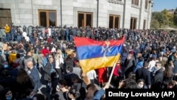 Protesters wave an Armenian national flag during a protest against an agreement to halt fighting over Nagorno-Karabakh, in Yerevan, Armenia, November 11, 2020