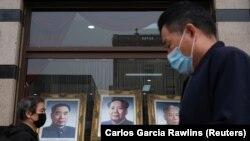 Люди в масках проходят мимо портретов покойных лидеров Коммунистической партии Китая (слева направо) Чжоу Эньлая, Мао Цзэдуна и Лю Шаоци.