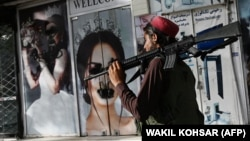 A Taliban fighter walks past a beauty salon with images of women defaced using spray paint in Kabul on August 18, days after the militant group seized the Afghan capital.