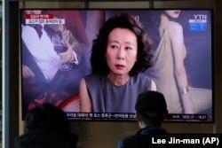 Emberek egy tévéképernyőn nézik a tudósítást Cson Dzsihjon Oscar-díjáról a Szöuli pályaudvaron, 2021. április 26-án.