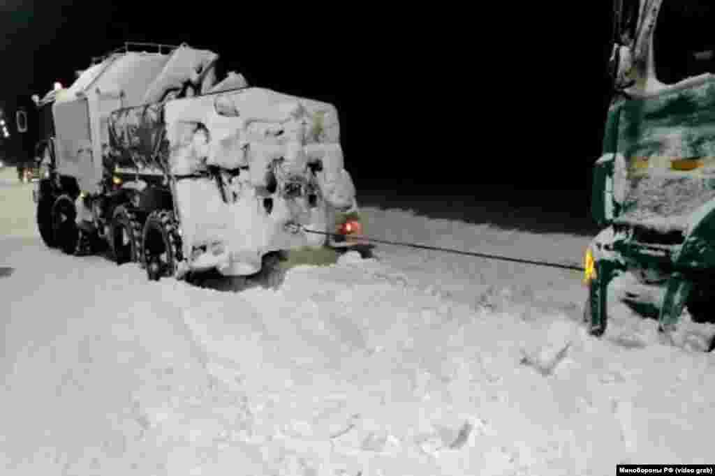 Автомобиль отряда подразделений армейского корпуса Черноморского флота России оказывает помощь по эвакуации застрявшего в снегу грузовика на трассе «Таврида»