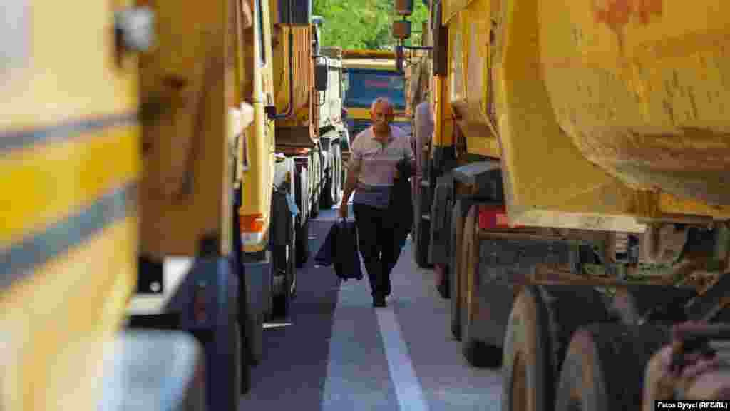 Мужчина проходит мимо грузовиков местных сербов, которые перекрыли дорогу к КПП«Ярина», 26 сентября
