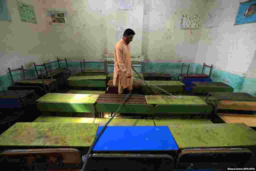 Рабочий убирает класс в школьном здании после того, как все учебные заведения закрылись в Пешаваре, Пакистан, на фоне увеличения случаев COVID-19