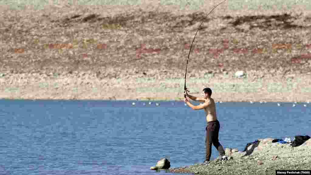 Мужчина ловит рыбу наСимферопольском водохранилище