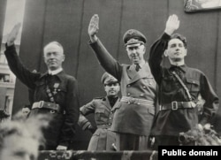 За пару месяцев до мятежа. Ион Антонеску (слева), Хориа Симпа (справа) и посол нацистской Германии приветствуют участников парада легионеров. Бухарест, 1940 год