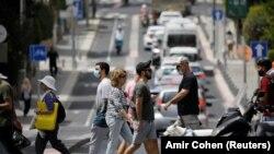 Këmbësorët kalojnë një rrugë në Tel Aviv të Izraelit më 18 Prill 2021.