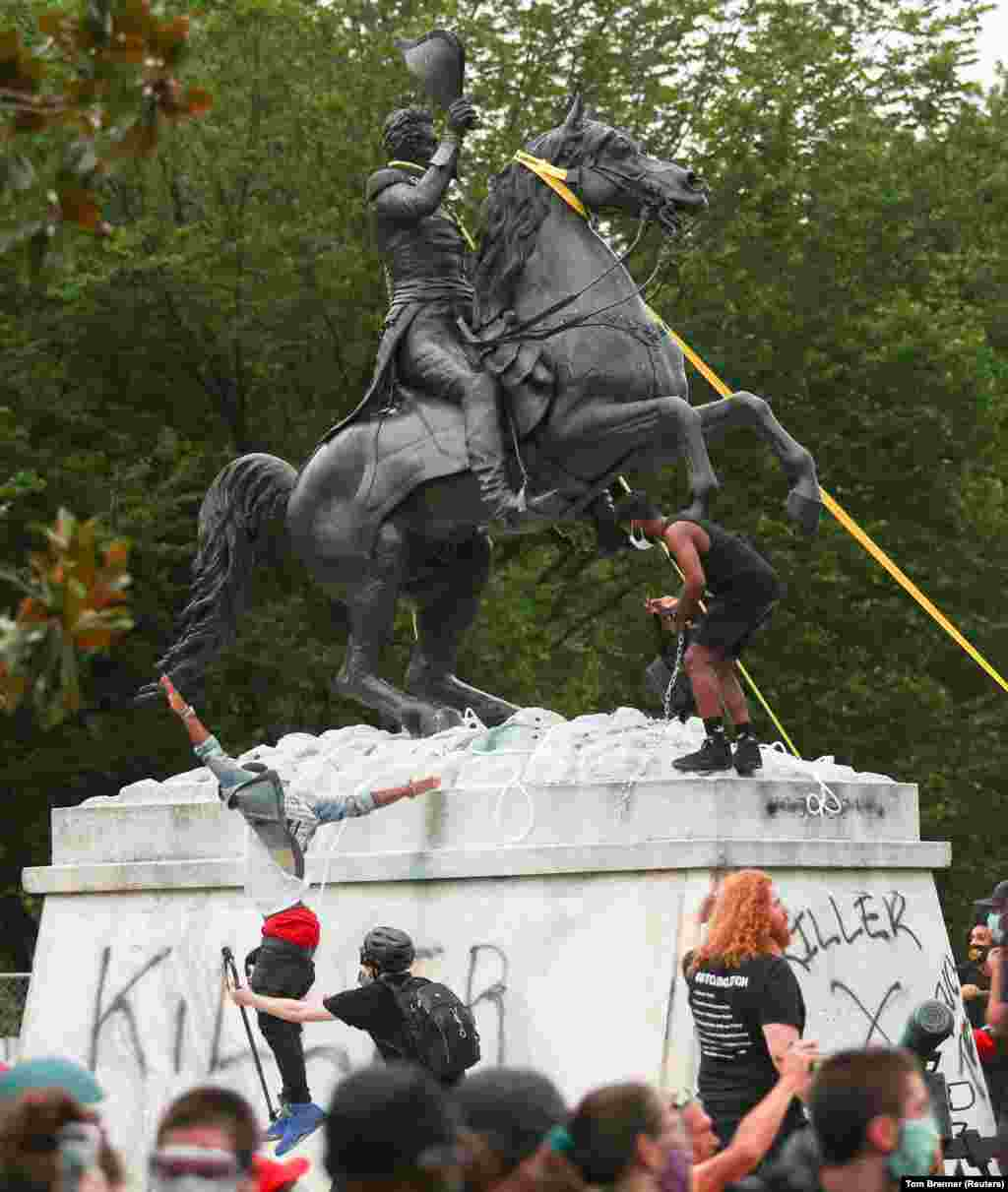 Protestors attempt to pull down the statue of U.S. President Andrew Jackson in the middle of Lafayette Park in front of the White House during racial inequality protests in Washington, D.C., U.S., June 22, 2020.